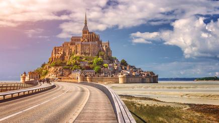 Beautiful panoramic view of famous Le Mont Saint-Michel tidal island with blue sky. Normandy, northern France