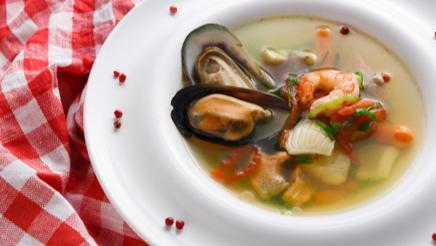 Seafood soup with white fish, shrimps and mussels in plate sprinkled with spices