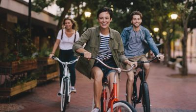 Three young people cycling down the street