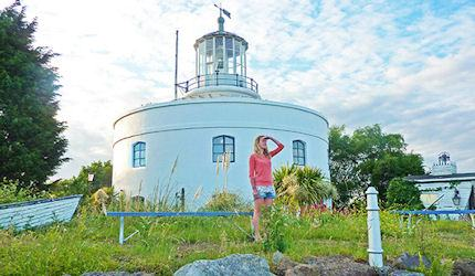 Young woman in a pink jumper and blue denim shorts at West Usk Lighthouse in Newport