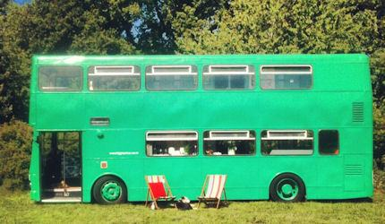 Big bright green bus with two beach chairs in front