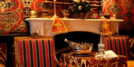 Two red and black striped chairs either side a small table covered in a red and gold table cloth. Table and chairs are in front a fire place
