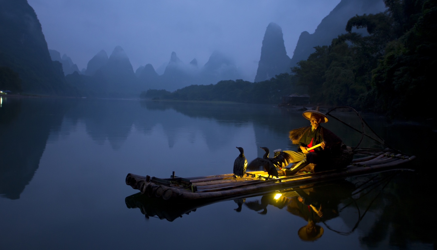 Home - Fisherman and osprey in Guilin China.