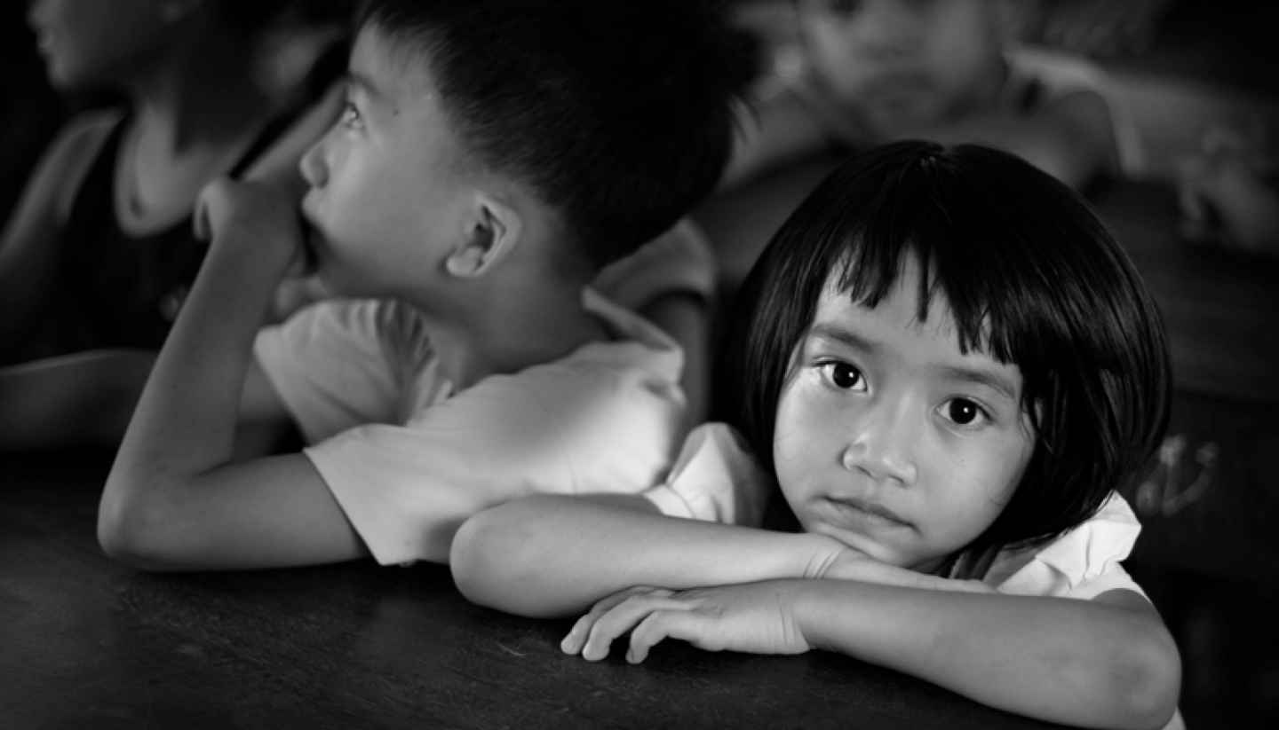 Does voluntourism do more harm than good? - Little girl sitting behind her desk, looking at the camera, surrounded by class mates who are looking in a different direction. Image is in black and white.