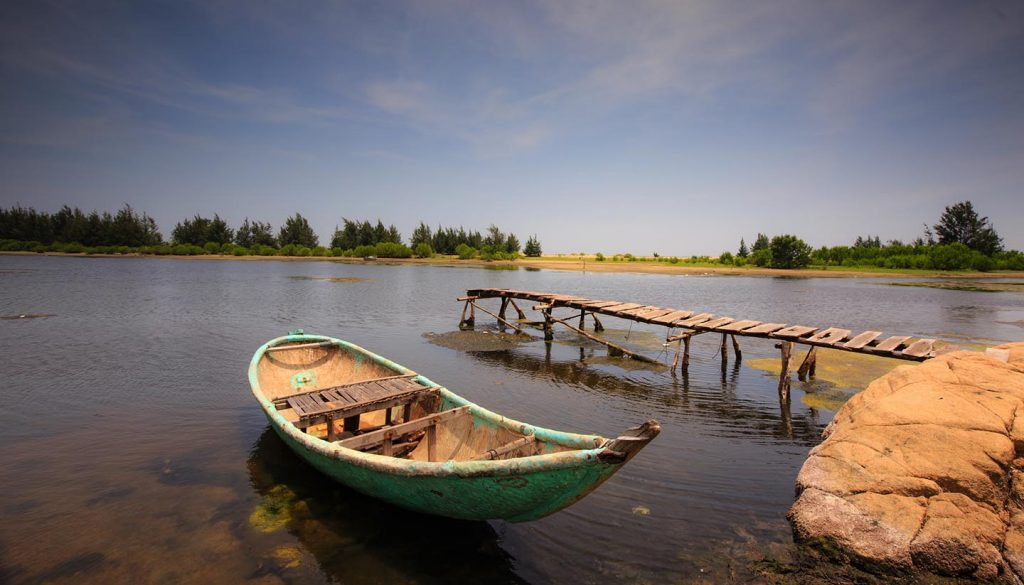 Guinea - Small pier with boat in a pond, Guinea