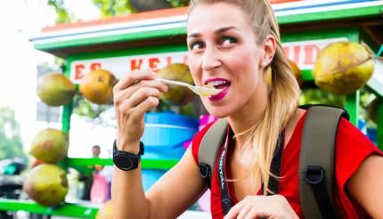 A tourist enjoying street food in Jakarta