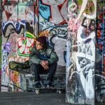 Skater sitting by graffitied walls