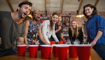 Friends playing beer pong