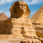 Sphinx with Giza pyramids in the background