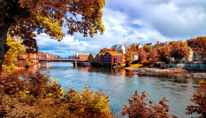 Top 5 places to see autumn foliage in Europe - View through autumn foliage to Nidelva river, Trondheim city, Norway
