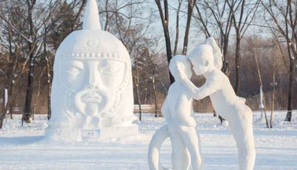 Snow sculpture of a girl whispering in a boy's ear