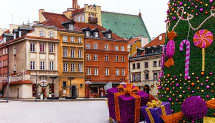 Famous Castle Square in Warsaw's Old Town in winter, huge Christmas tree on right side, colourful houses and buildings all around