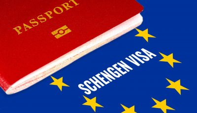Red passport on Europe flag background with Schengen Visa in the circle of stars