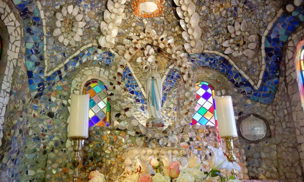 The main altar is beautifully decorated with pebbles, seashells and pieces of china