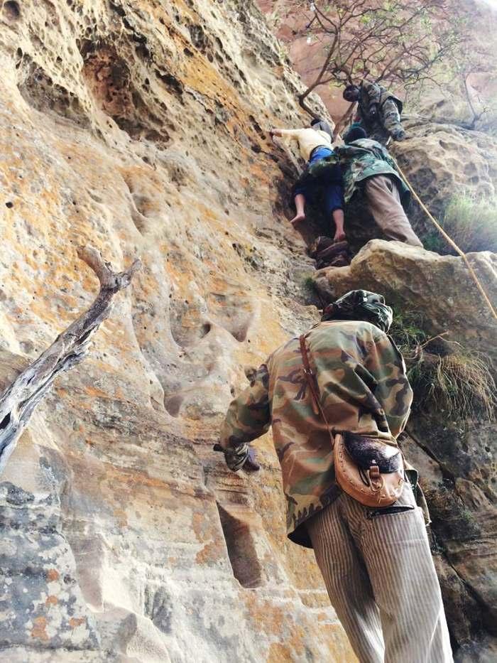 Locals helping tourists climb a 10m vertical wall