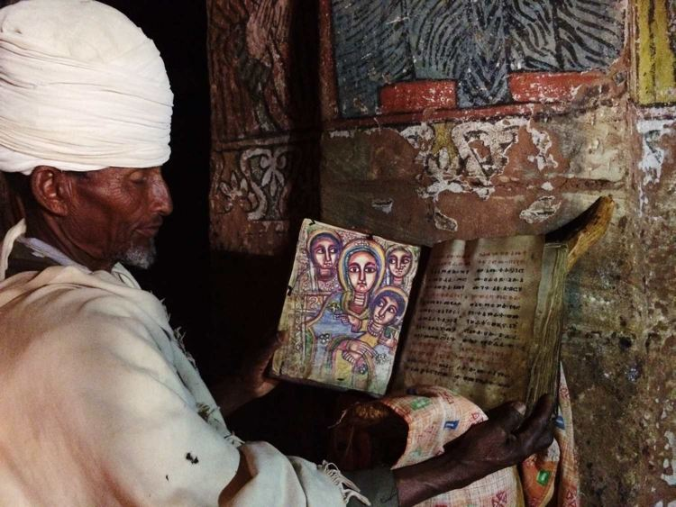 The priest holding the holy book Teamre Mariam (Miracle of St Mary)