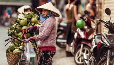 Vietnamese woman sells cocoes on the street