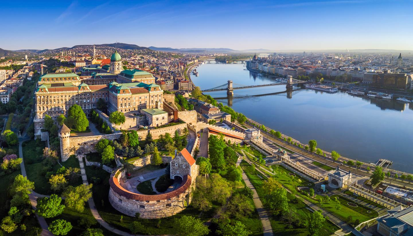 City Highlight: Budapest - Aerial panoramic skyline view of Buda Castle Royal Palace with Szechenyi Chain Bridge, St.Stephen's Basilica, Hungarian Parliament and Matthias Church at sunrise with blue sky