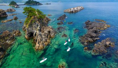 People standup paddle boarding in Takahama, Japan