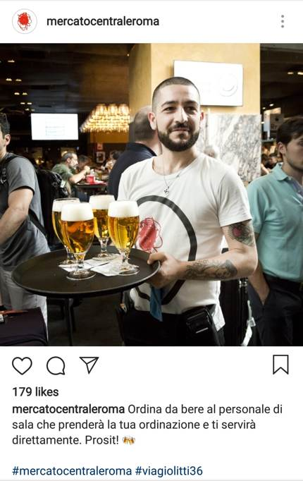 Happy waiter with a tray of beer at Mercato Centrale Roma