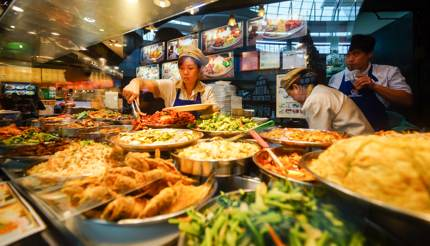 The Shoppes at Marina Bay Sands - workers preparing food behind a display of dishes
