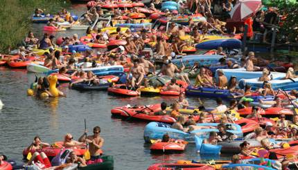 People drinking beer on inflatable rubber boats on a river