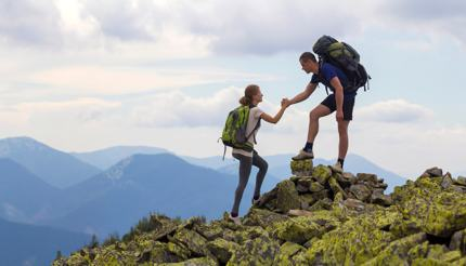 Man helping woman companion while hiking