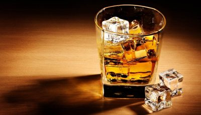 glass of whisky with ice cubes inside