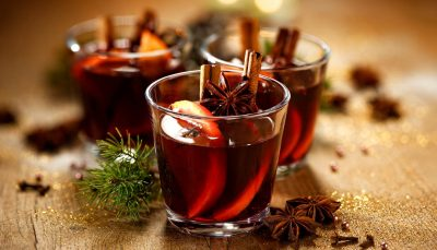 Glasses of mulled wine with orange slices and cinnamon sticks