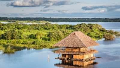 Aerial view of wooden hut on a river in the Amazon rainforest