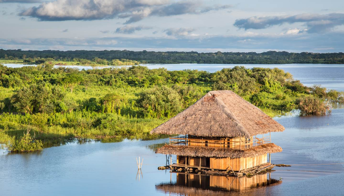 Peru: Secrets of the Amazon - Aerial view of wooden hut on a river in the Amazon rainforest