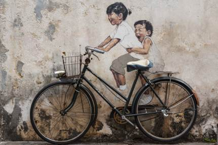 Wall art of a brother and sister riding a bike