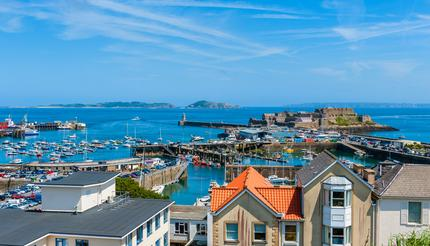 View over Saint Peter Port Harbour, Guernsey. The Islands of Sark & Herm are visible in the distance.
