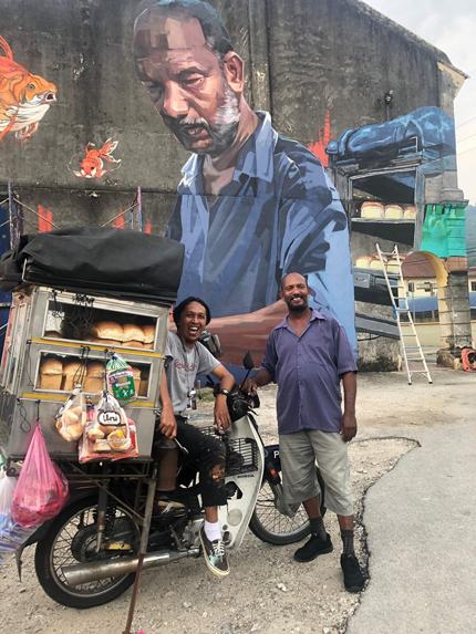 Artist Acit Raman Abdullah (left) with the bread seller Muniandi (right) in front of the giant mural