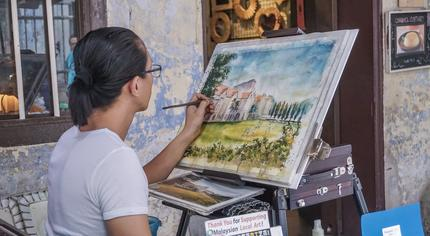 A young artist draws and sells his work in Ipoh