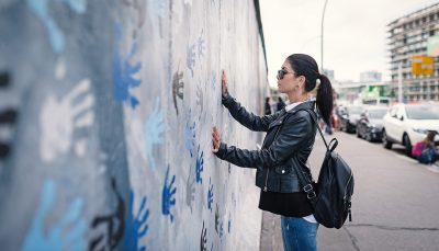 Woman with hands on Berlin Wall