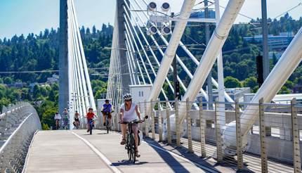 People cycling on Tilikum Bridge, Portland, Oregon