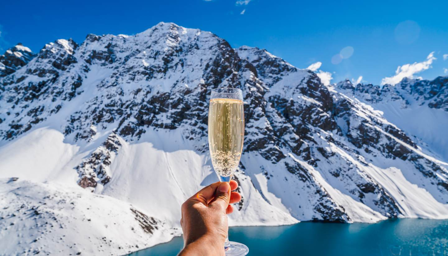 Top 10 luxury ski resorts around the world - Person holding champagne - background mountain