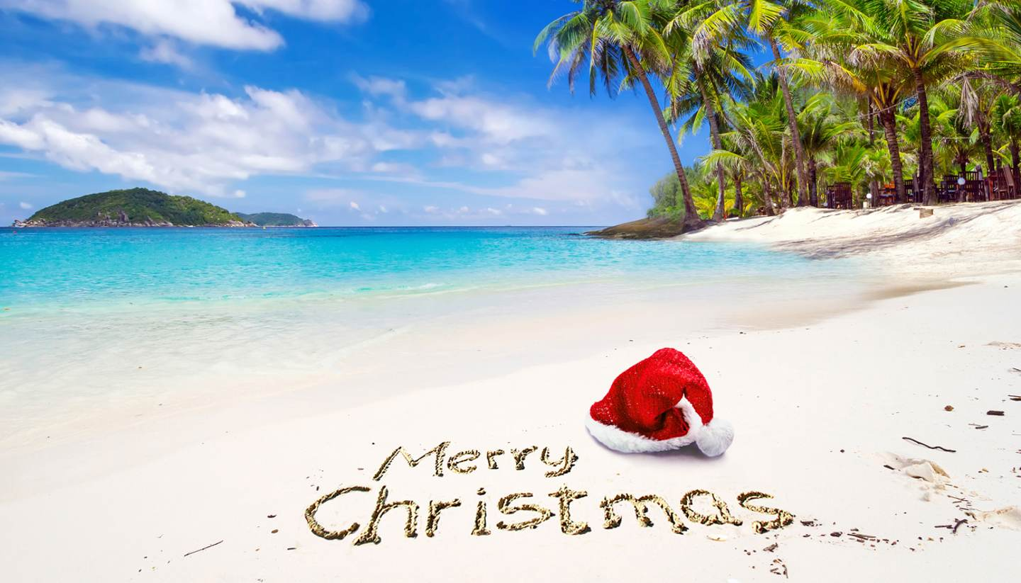 Merry Christmas from World Travel Guide - Santa hat on tropical beach